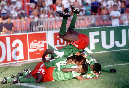 1990 World Cup Finals. Second Phase. Naples, Italy. 23rd June, 1990. Cameroon 2 v Colombia 1. Cameroon captain Stephen Tataw jumps on top of his teammates as they celebrate their second goal scored by Roger Milla.